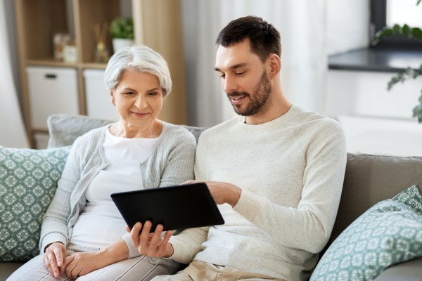 Older woman sitting on a couple with her adult son looking at a tablet.