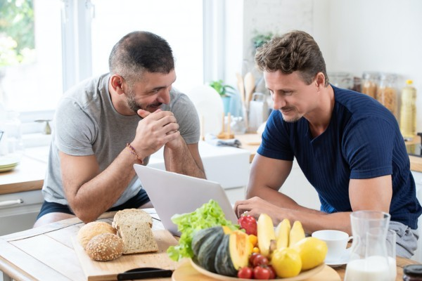 Two men sitting at a table with a laptop and snacks.