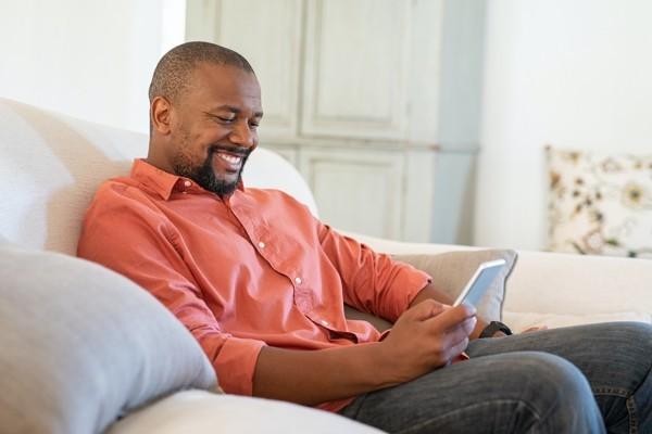 Smiling man looking at his phone.