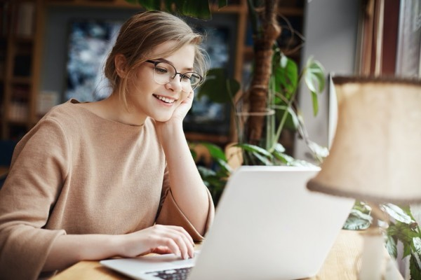 Smiling woman typing on a laptop.