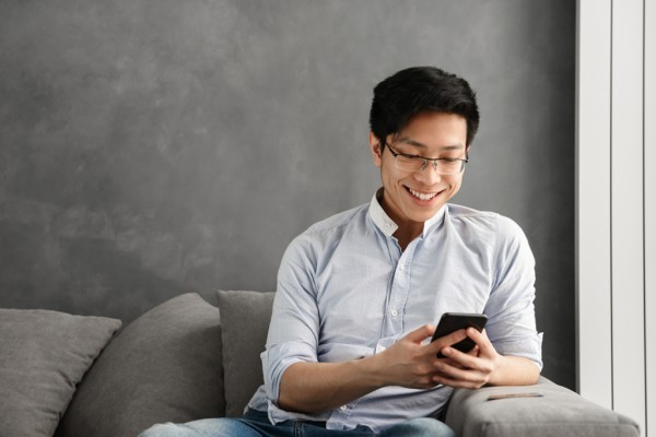 Smiling man sitting while looking at his phone.