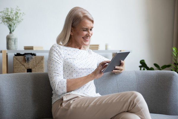 Smiling woman sitting while looking at her tablet.