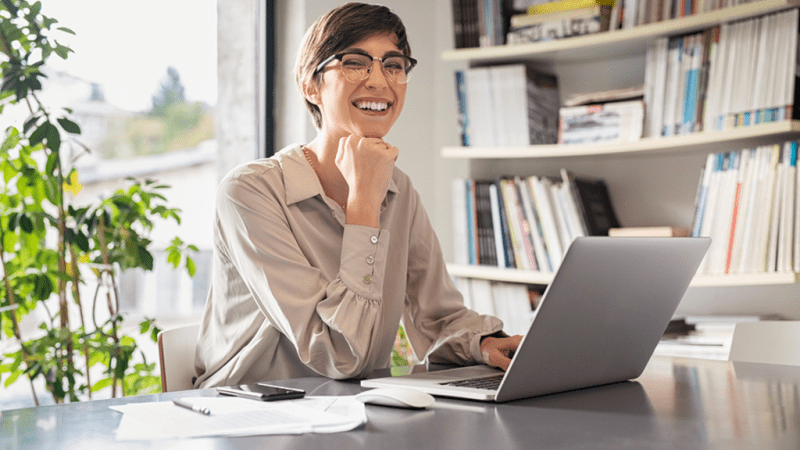 Smiling woman at her desk in front of a computer.