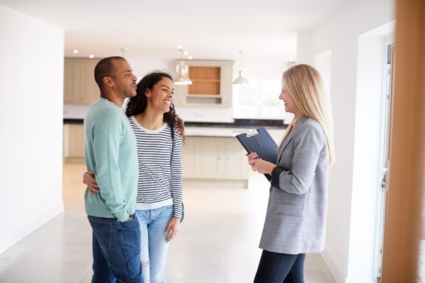 Couple meeting with a realtor in a new home.