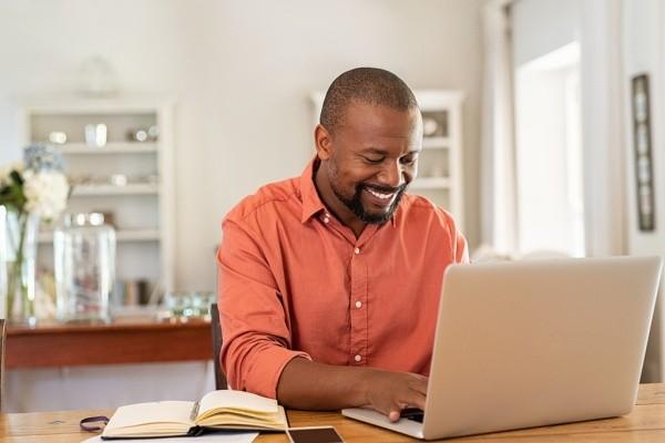 Smiling man reading his social media post using a laptop computer.